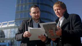 Two young businessmen discussing document. Professional shot on BMCC with high dynamic range. You can use it e.g in your commercial video, business or office stock video footage