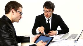 Two young businessmen discussing project at stock footage