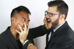 Two young businessmen fighting. On a studio background stock photography