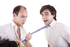 Two young businessmen grasping his tie Stock Images