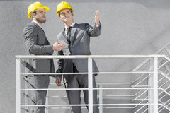 Two young businessmen in hard hats discussing on stairway Stock Image