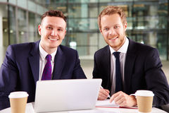 Two young businessmen having coffee, using a laptop computer Royalty Free Stock Photography