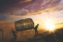 Two young businessmen lifting success word. Two young businessmen lifting a stone with success word while climbing on the cliff, Shot at sunset time Royalty Free Stock Images