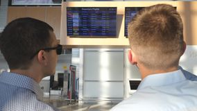 Two young businessmen looking at flight schedule at airport. Business man pointing something to his colleague in. Sunglasses at timetable board screen. Checks stock footage