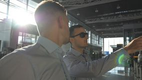 Two young businessmen looking at flight schedule at airport. Business man in sunglasses pointing something to his. Colleague at timetable board screen. Checks stock footage