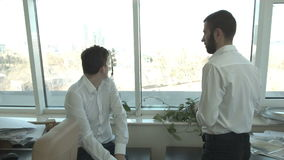 Two young businessmen are looking out the window discussing the construction of buildings stock video footage