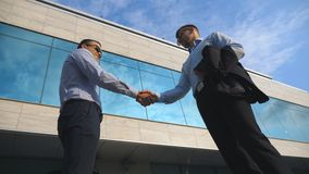 Two young businessmen meeting near office and greeting each other. Business man passing a black briefcase to his partner. Colleagues shake hands outdoor in the stock video footage