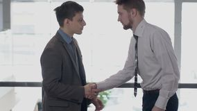 Two young businessmen is meeting, shaking hands in modern office. Two young businessmen is meeting, shaking hands in modern office, friendly professionals stock video