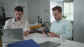 Two young businessmen at the office. Concentrated contemplative man at the working place using digital tablet. His partner young professional worker search stock footage