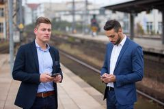 Two businessmen with phones waiting at train station. Two young businessmen with phones waiting at train station Royalty Free Stock Images