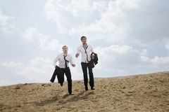 Two young businessmen running and exhausted in the desert, holding jackets Stock Image