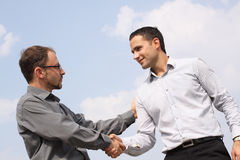 Two young businessmen shaking hands. Closeup of two young businessmen shaking hands over a deal on sky background royalty free stock image