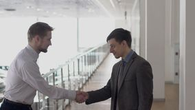 Two young businessmen shaking hands in office gallery, slow motion. Concept: people, business, bargain stock video footage