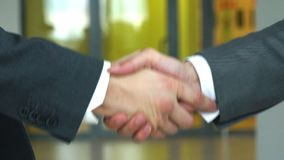 Two business men shaking hands slow motion. Two young businessmen shaking hands in office stock video
