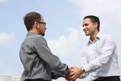 Two young businessmen shaking hands over a deal. Closeup of two young businessmen shaking hands over a deal on sky background royalty free stock image