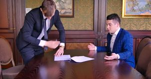 Two young businessmen sign a contract, curse, scream, fight. Office, nerves, torn deal, inappropriate conditions, bad