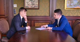 Two young businessmen sign a contract. Start of negotiations, etiquette, courtesy, discuss contract terms. Business
