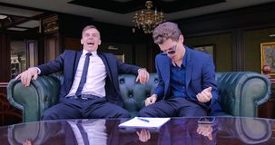 Two young businessmen are sitting in a green leather armchair in luxury apartments in suits and playing imaginary. Musical instruments stock video