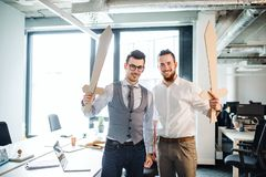 Two young businessmen with swords in an office. A competition concept. Two young businessmen with cardboard swords in an office. A competition concept royalty free stock image