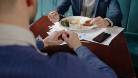 Two young businessmen are talking, eating food, sitting opposite at table in restaurant. Conduct dialogue about work, enjoy delicious meal. Enterprising people stock footage