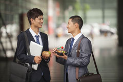 Two young businessmen talking and having a lunch outdoor Stock Images