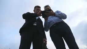 Two young businessmen talking and using tablet pc outdoor. Business men working on digital tablet outside with sky at. Background. Colleagues applying mobile stock video footage
