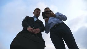 Two young businessmen talking and using tablet pc outdoor. Business men working on digital tablet outside with sky at. Background. Colleagues applying mobile stock footage