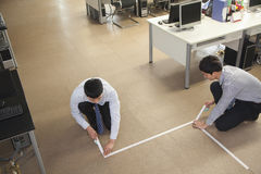 Two young businessmen taping up the floor in the office Royalty Free Stock Photos
