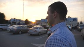 Two young businessmen walking in auto parking at sunset time. Business men commuting to work together. Confident guys stock video