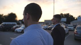 Two young businessmen walking in auto parking at sunset time. Business men commuting to work together. Confident guys. Being on his way to office. Colleagues stock video footage