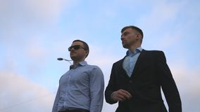 Two young businessmen walking in city with blue sky at background. Business men commuting to work together. Confident stock video footage