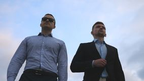 Two young businessmen walking in city with blue sky at background. Business men commuting to work together. Confident. Guys being on his way to office Stock Image