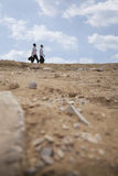 Two young businessmen walking through the desert, in the distance Stock Photo