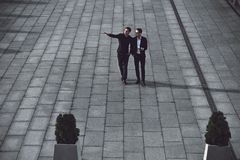 Two young businessmen walking in the street royalty free stock photography