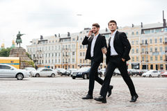 Two young businessmen walking and talking on mobile phone Stock Photography
