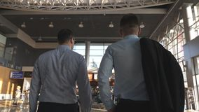 Two young businessmen walking in terminal at airport. Men stepping at business center. Rear back view. Slow motion.  stock footage