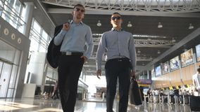 Two young businessmen walking in terminal at airport and talking. Men stepping at business center and speaking. Front. View. Slow motion stock video