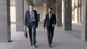 Two young businessmen walking to the office together stock video