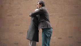 Two young businessmen meeting in the street and shaking hands. Two young businessmen wearing coats and scarves meeting in the street and shaking hands. Ten stock footage