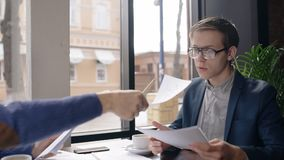 Two young businessmen is working on blueprint, sitting at table in cafe, partner passes documents to man, business. People work with project during coffee break stock footage