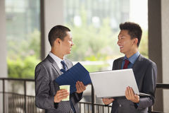 Two young businessmen working outdoor, looking at each other Stock Images