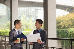 Two young businessmen working outdoor, looking at each other and smiling Royalty Free Stock Image
