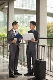 Two young businessmen working outdoor, looking at each other and smiling stock image