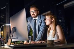 Businesspeople in the office at night working late. Royalty Free Stock Images