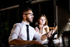 Businesspeople in the office at night working late. Royalty Free Stock Photos