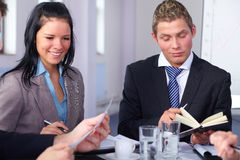 Two young businesspeople sitting at table Stock Images