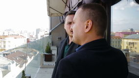 Two young businesspeople talking on the balcony in a restaurant stock video footage