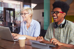 Two Young Businesspeople Working On Laptop In Coffee Shop Royalty Free Stock Images