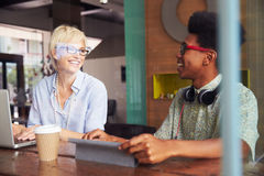 Two Young Businesspeople Working On Laptop In Coffee Shop Royalty Free Stock Photography