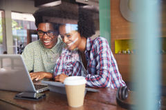 Two Young Businesspeople Working On Laptop In Coffee Shop Stock Images